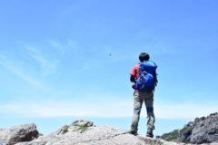山頂で空を見上げる男性