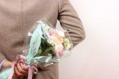 花束を後ろ手に隠し持つ男性