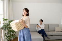 洗濯を干す不機嫌な妻と携帯を触っている夫