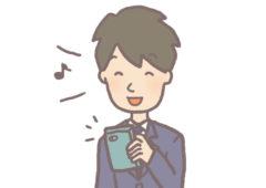 携帯を嬉しそうに触る男子学生