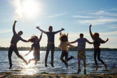 海辺でジャンプする若者たち