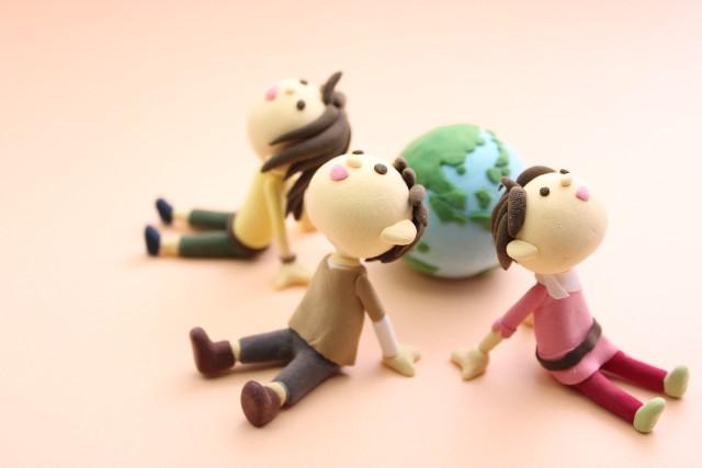 地球儀のそばに座り上を見上げる子ども達