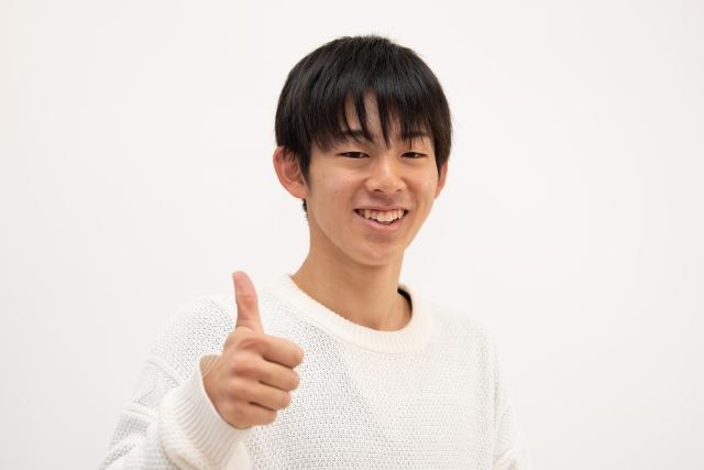 親指を立ててGoodポーズをする高校生男子