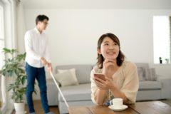 掃除をする夫とコーヒーを飲む妻